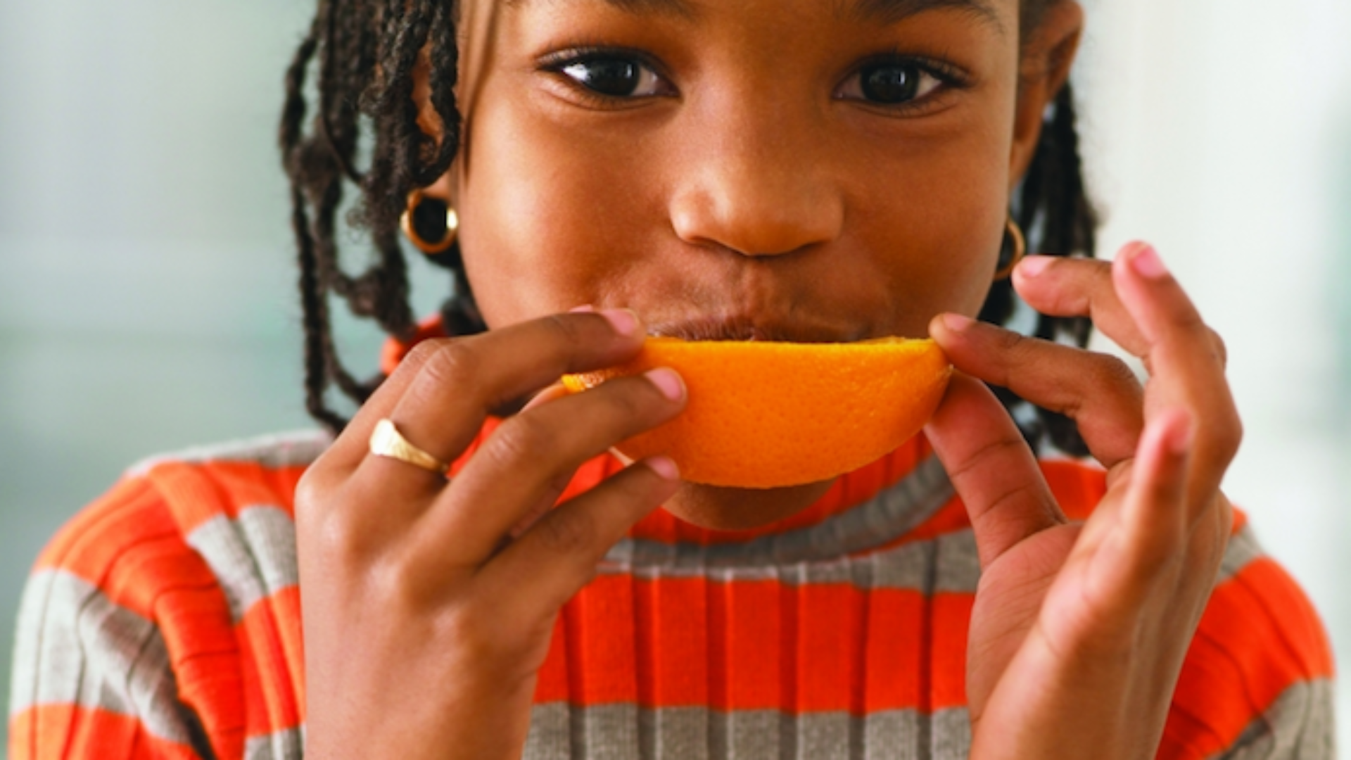 Girl eating orange