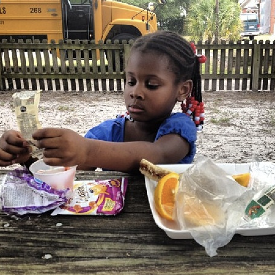 Girl eating outside near school bus