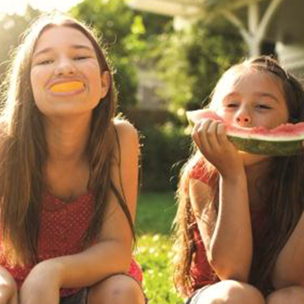 Two girls eating fruit